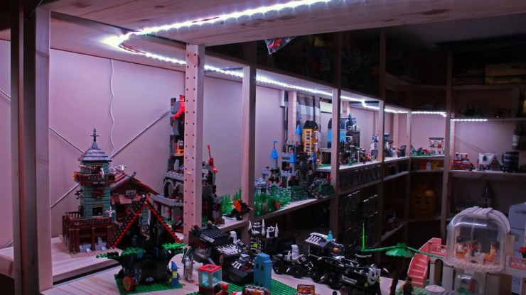 A long strip of white LEDs illuminating a dark room filled with Lego bricks.