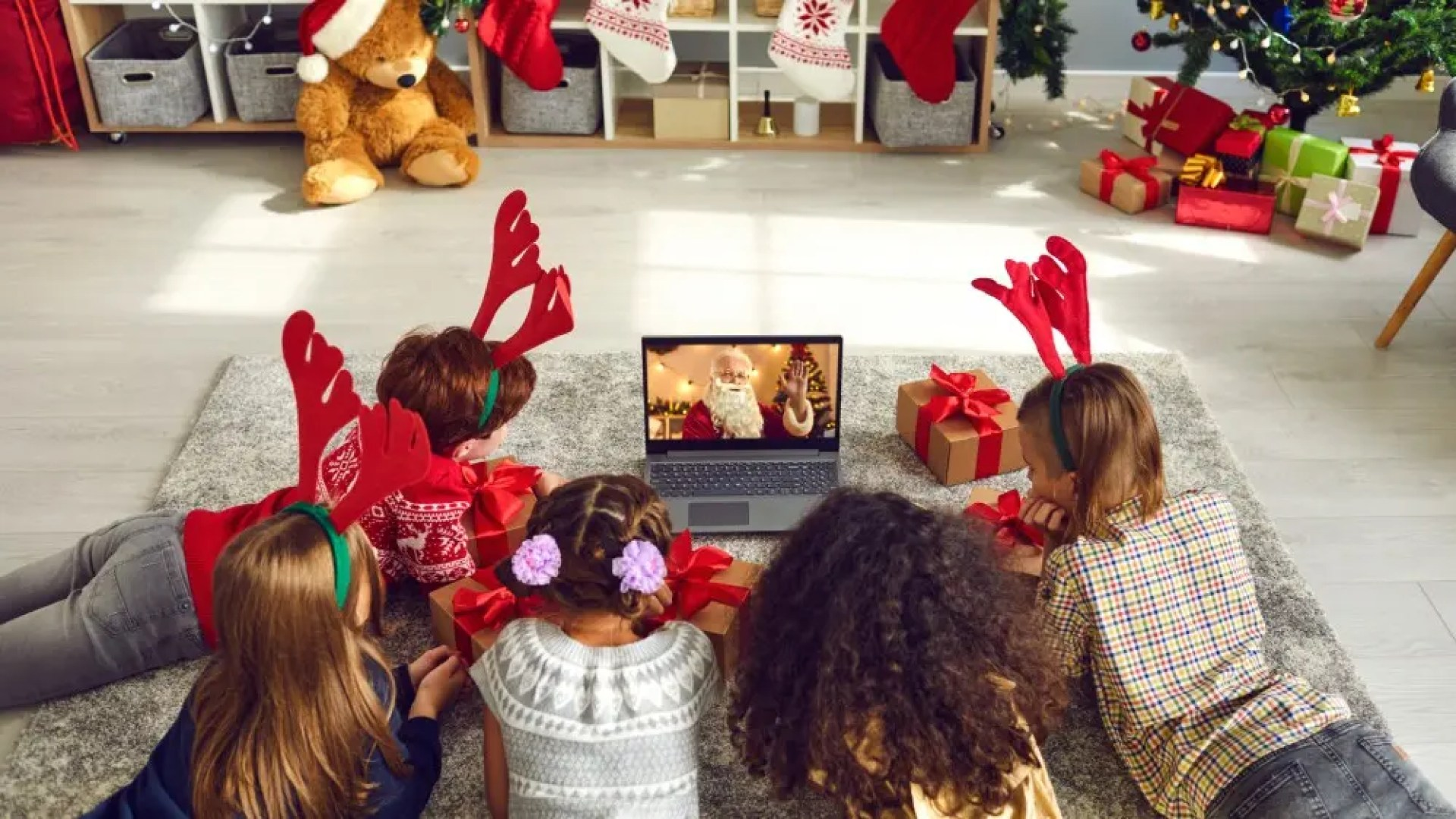 A group of children watching a video chat with Santa Claus using a laptop in a festive decorated home