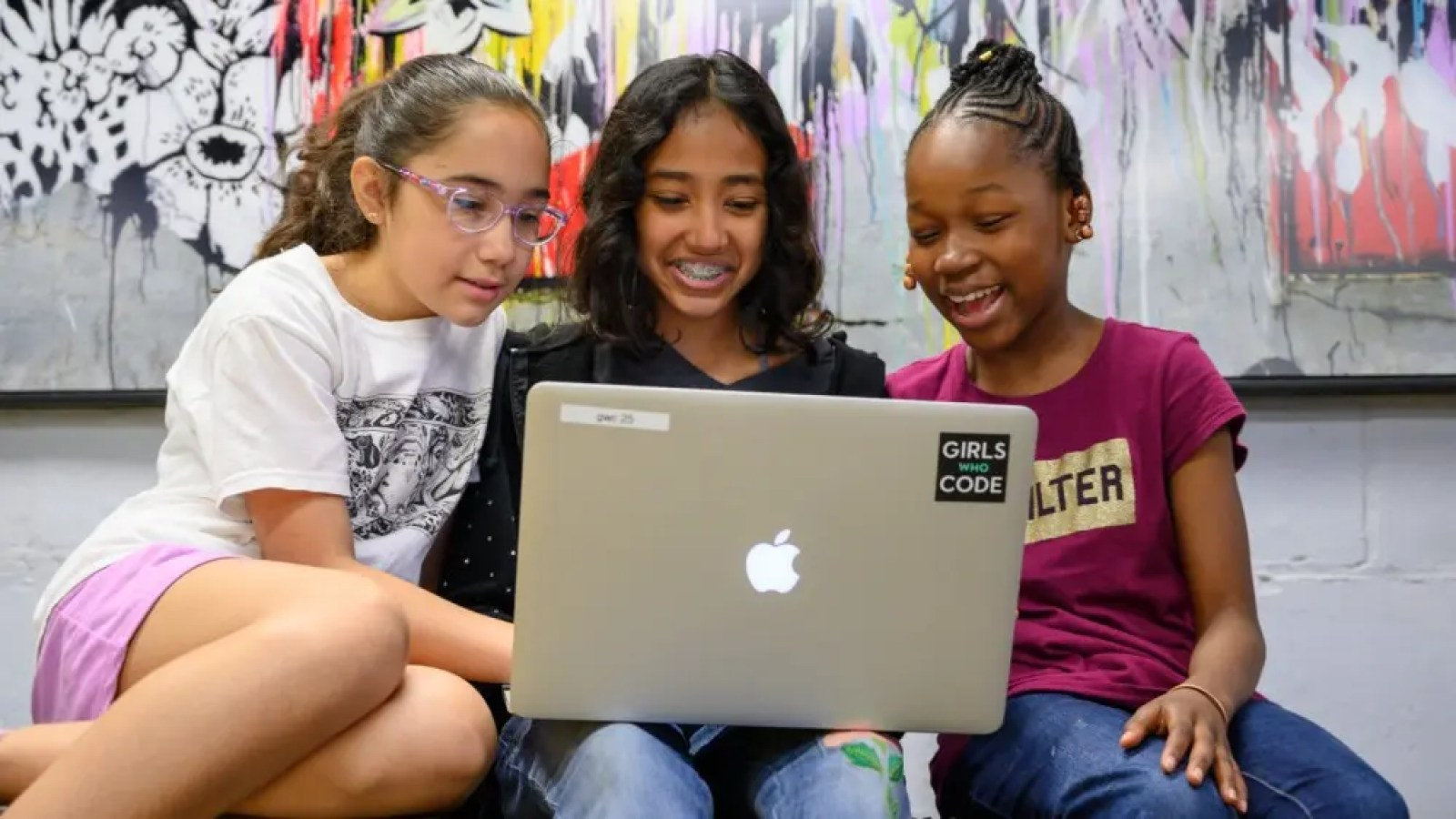 Three girls looking at computer code and smiling