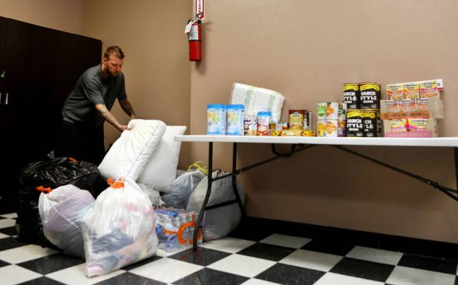 Owner And Artist Joe Riley Of Inner Visions Tattoo With Donated Goods At His In