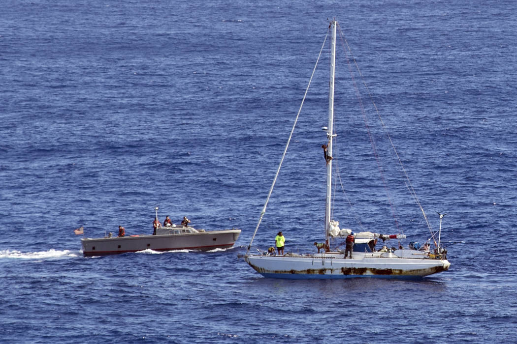 In this Wednesday, Oct. 25, 2017 photo, sailors from the USS Ashland approach a sailboat with two Honolulu women and their dogs aboard as they are rescued after being lost at sea for several month ...