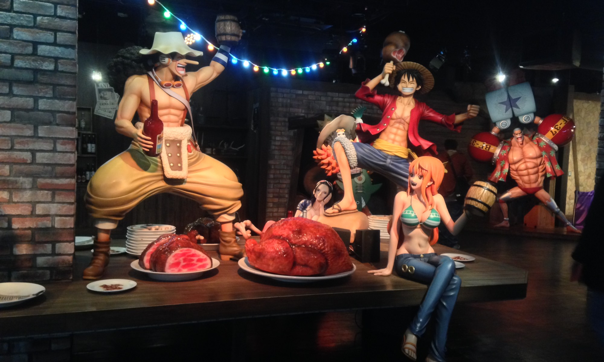 The Strawhats celebrating around a table with Nami sitting holding a beer mug, Luffy and Usopp dancing around and Robin sitting and looking at them fooling around
