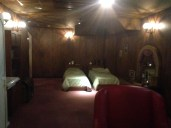A room with a twin bed at the center, a mirror to the right and the door to the left; the lighting is a bit dim, there is a pink carpet on the floor and the walls are wooden