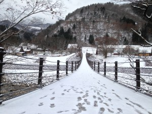 A hanging bridge at the center covered in snow with some footsteps dotting the edge; A snow sprinkled mountain and cottages on the other side