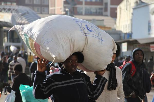 A women carrying a sack on her head. Image credit zimnewsblog.com
