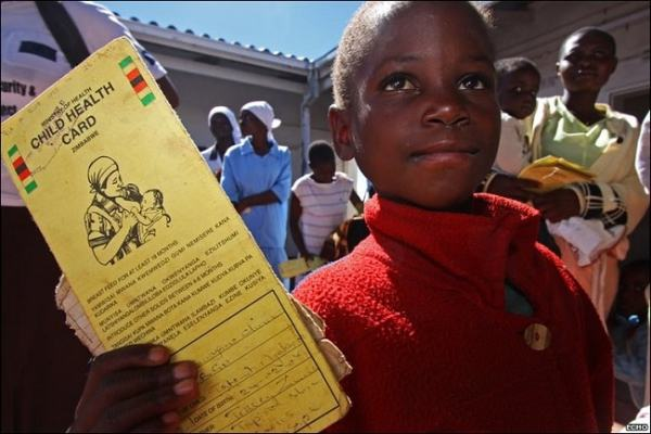 A child holding a clinic card. Image credit BBC