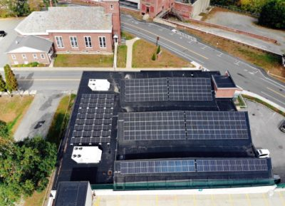 A drone shot shows three roof peaks covered in solar panels on the roof of Claremont MakerSpace.
