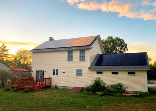 A setting sun reflects off the solar panels on the roof of Chris and Jill's house.