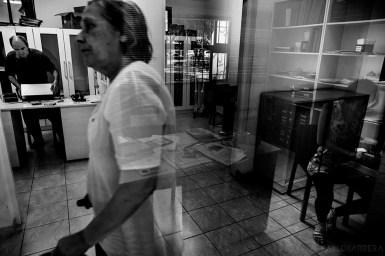 """Santiago Duran, socio activo ciego, prepara sus pertenencias para retirarse mientras Silvia Monteverde, empleada no ciega de la biblioteca, transita por los pasillos de la misma. Del lado derecho se refleja por un vidrio a otra de las empleadas de la biblioteca, la diseñadora grafica Vanesa Potes, que posee la """"enfermedad de Wilson"""", enfermedad que se manifiesta con síntomas como espasmos musculares constantes, visión reducida y dificultad para el habla, entre otros.(©Pablo Barrera)"""