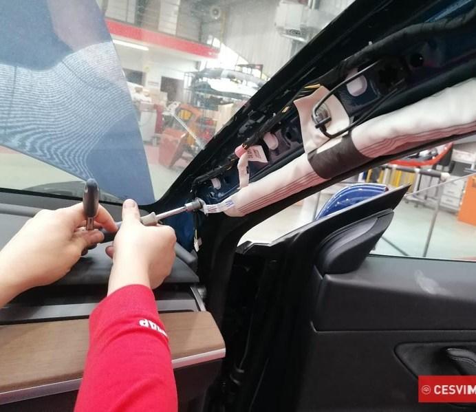 Técnico de taller sustituyendo el airbag de cortina del Model 3.