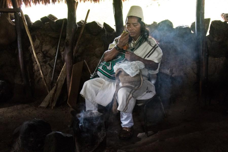 Un indígena arhuaco descansa con sus dos mochilas sobre sus piernas, mientras tuesta algunas hojas. Foto: Aitor Sáez
