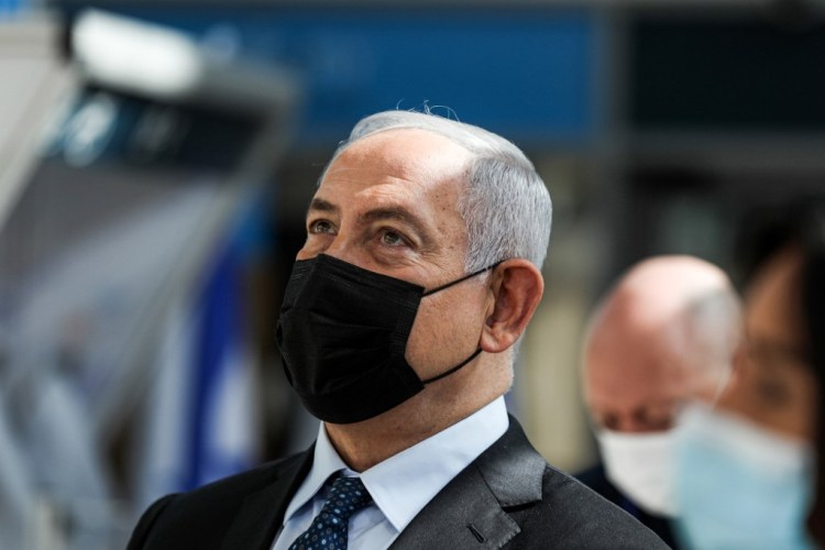 Israeli Prime Minister Benjamin Netanyahu attends while mask-clad the inauguration of a COVID-19 coronavirus rapid testing centre at Ben Gurion International Airport in Lod on November 9, 2020. - Netanyahu inaugurated the rapid coronavirus testing centre at Israel's main international airport, meant to ease travel in and out of the country. The new set-up allows travellers to give a sample at the terminal and have it analysed at an on-site lab, with the result ready in 5 1/2 to six hours as the traveller waits, costing 135 shekels ($40). (Photo by ATEF SAFADI / POOL / AFP)