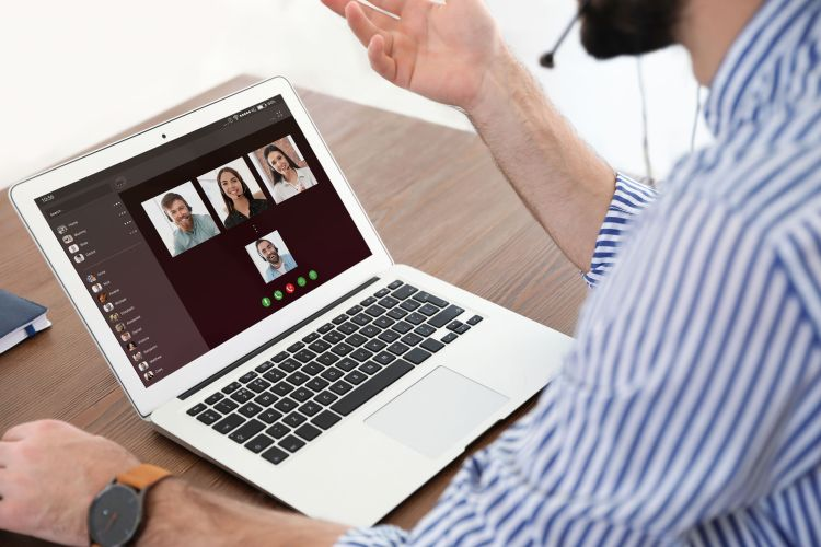 Man having video chat with colleagues at table in office, closeup