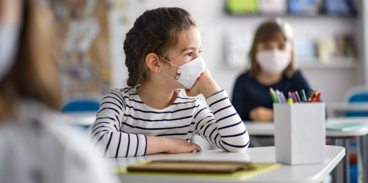 Bored child with face mask back at school after covid-19 quarantine and lockdown.