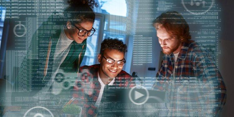 Equipo en trabajo de programadores, codificando un nuevo juego online de casino. Tres personas: una mujer y dos hombres.