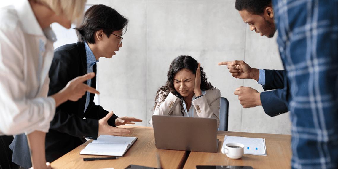 Conflicto en el trabajo. Infeliz mujer de negocios victimizada cubriendo orejas sin escuchar a colegas agresivos gritando a su sentado en el escritorio en la oficina moderna. - mobbing