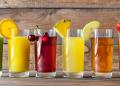 Surtido de jugos de frutas en vasos de cristal. De izquierda a derecha: kiwi, naranja, cereza, piña, manzana y fresa.