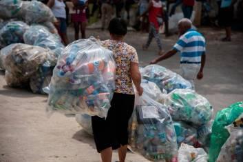 Señora camina con dos fundas plásticas repletas de botellas plásticas