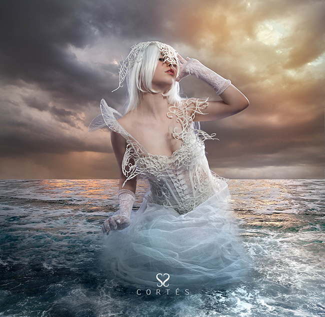 the forces of nature, blonde woman on the rocks with the sea raging and powerful