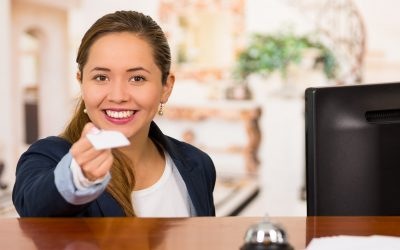 Young brunette hotel receptionist with friendly smile handing over key to client across desk, customers point of view.