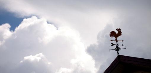 Girouette metallique en forme de coq sur fond de nuages