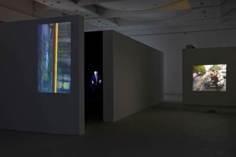 """Fig. 5 : Vue de l'espace ouvert (dit l'Agora), exposition « Entrevoir. Robert Cahen ». De gauche à droite : La Barre jaune (2014), Le Maître du temps – Pierre Boulez dirige """"Mémoriale"""" (2011), La traversée du rail (2014), © Nicolas Fussler."""