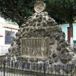 "Monument on Ciudad Vieja church plaza depicts founding ""here on this site the city of Santiago."""