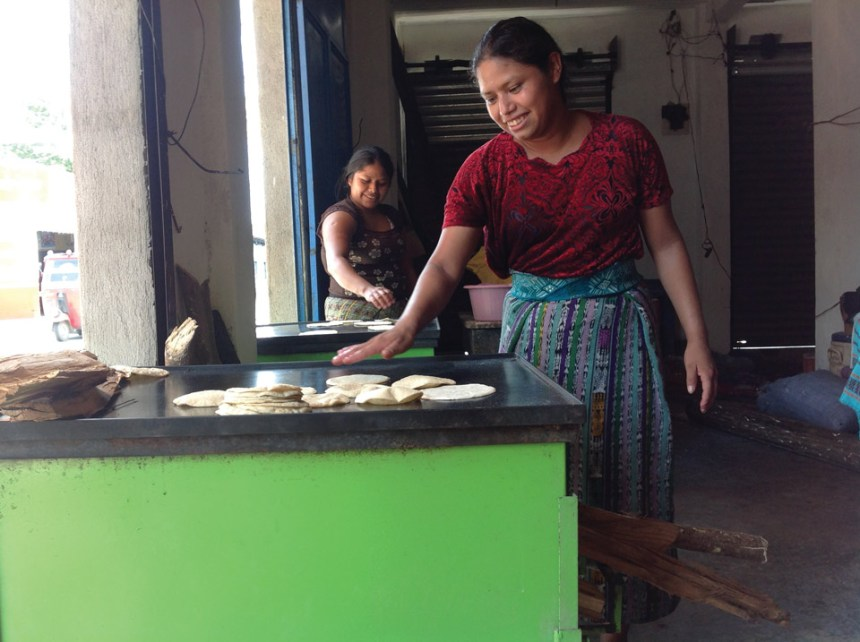 Women use the new stove to make tortillas for sale.
