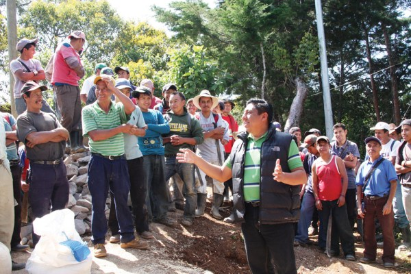 Project manager greeting workers at site of water distribution tank.