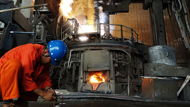 A Chinese steelworker works in front of a furnace at the Dalian Special Steel Company Ltd. in Dalian, northereastern China's Liaoning province, June 20, 2018.
