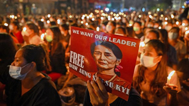 A Myanmar protester holds a poster with an image of detained civilian leader Aung San Suu Kyi during a candlelight vigil to honor those who have died during demonstrations against the military coup, in Yangon, March 13, 2021. AFP