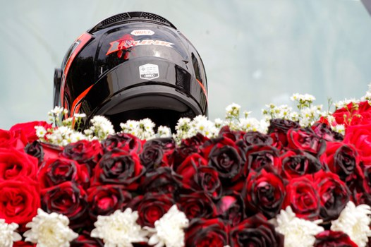 The bullet-pierced motorbike helmet of slain protester Mya Thwe Thwe Khine, adorns her funeral floral display in Naypyidaw, Feb. 21, 2021.