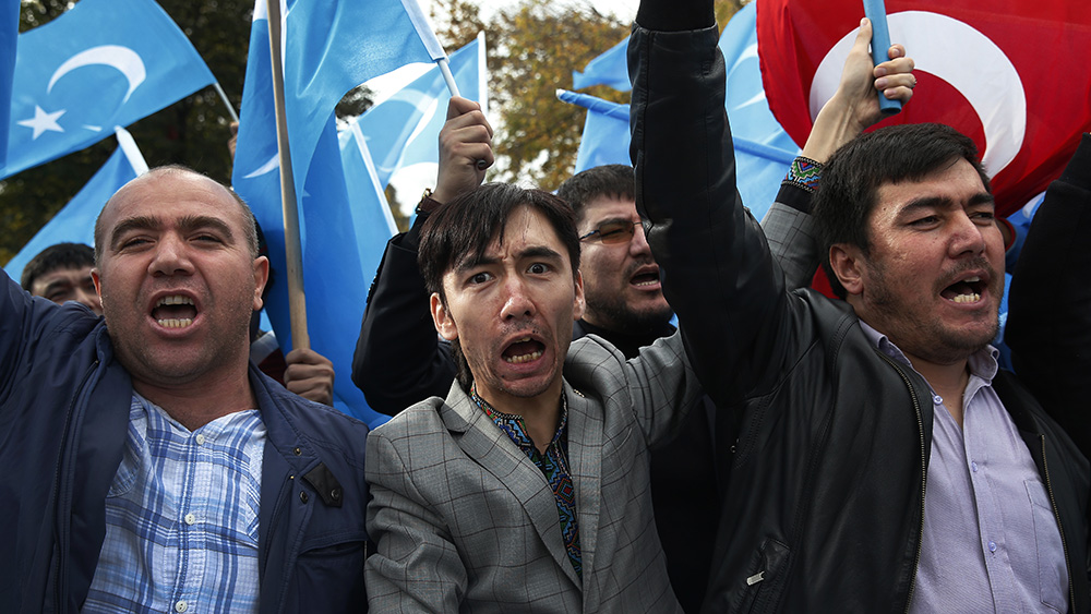 Members of the Uyghur community in Turkey carry flags and chant slogans during a protest in Istanbul, Nov. 6, 2018.