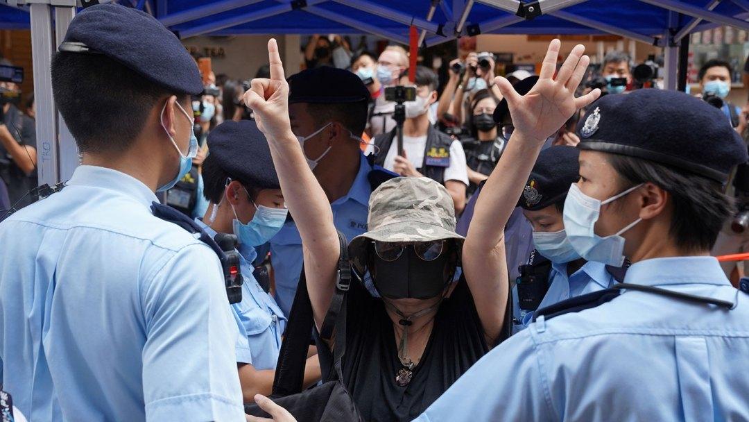 """2021年7月1日,是香港主权移交24周年,兼中国共产党成立100周年,铜锣湾警方拒绝允许举行抗议集会后,一名妇女在铜锣湾举起双手,象征""""五个要求,不能少一个""""。(路透社)"""