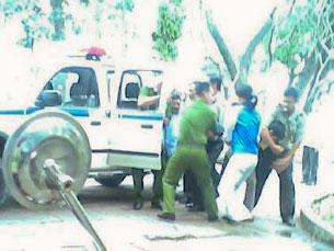 Hình công an đang ôm cổ cưỡng chế anh Vũ Văn Tĩnh, vì anh ngồi thiền Pháp Luân Công ôn hòa tại công viên Lê Văn Tám ngày 02/02/2012