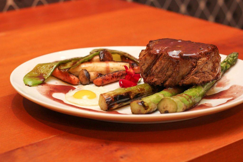 Filé, alto, grelhado e molho do Chef, acompanhado de vagem torta, palmito, cogumelos, cenoura, aspargos, farofa da casa e ovo de cordorna frito.