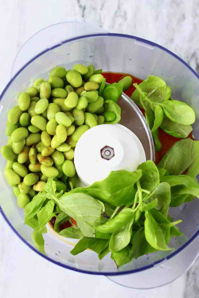 Edamame beans, basil and soy sauce in a food processor against a marble background