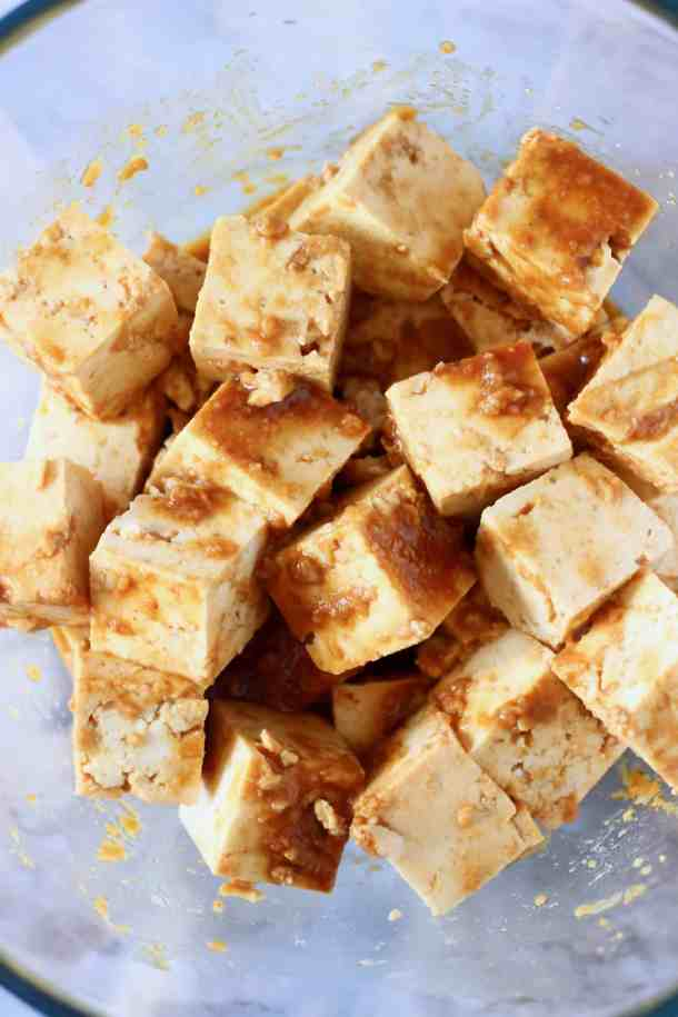 Photo of cubes of tofu marinating in a peanut sauce in a glass bowl