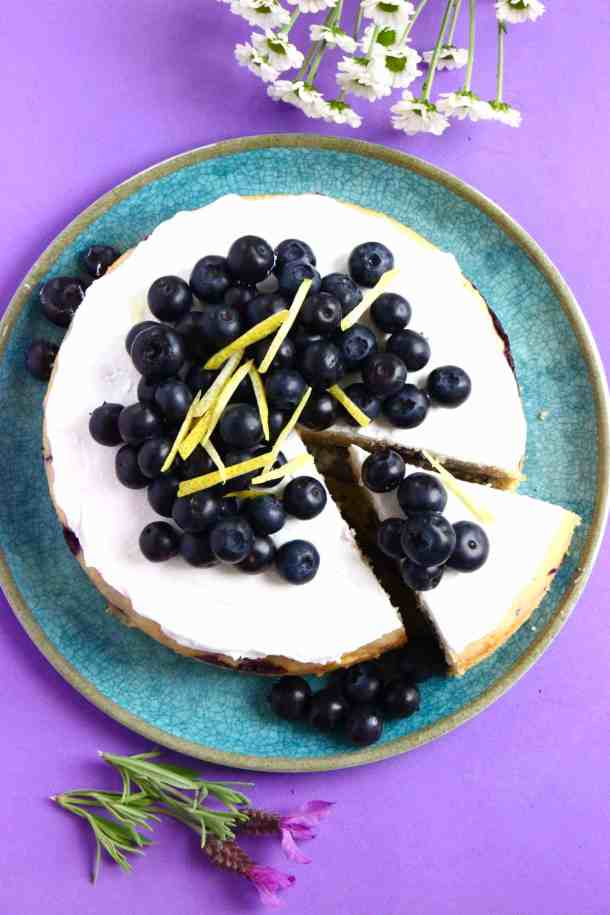 Photo of a cake topped with white frosting and fresh blueberries on a blue plate and a purple background taken from above