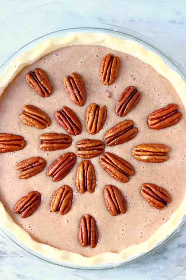 Photo of a raw pie crust in a glass pie dish filled with a brown filling topped with pecan nuts
