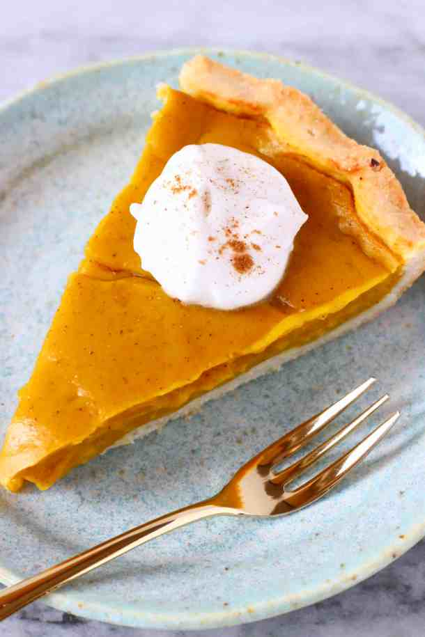 Photo of a slice of pumpkin pie topped with cream and sprinkled with cinnamon on a blue plate with a gold fork