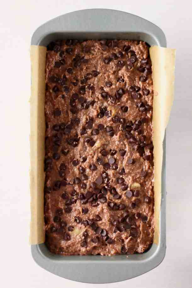 Raw chocolate banana bread batter topped with chocolate chips in a silver loaf tin lined with brown baking paper against a white background
