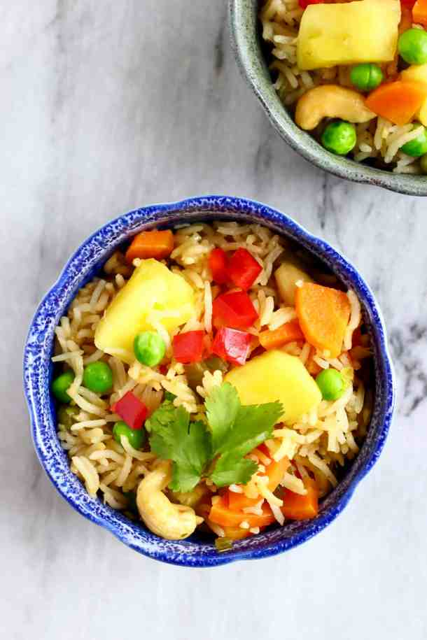 Photo of a small blue bowl with rice, green peas, red pepper, carrots and pineapple chunks against a marble background