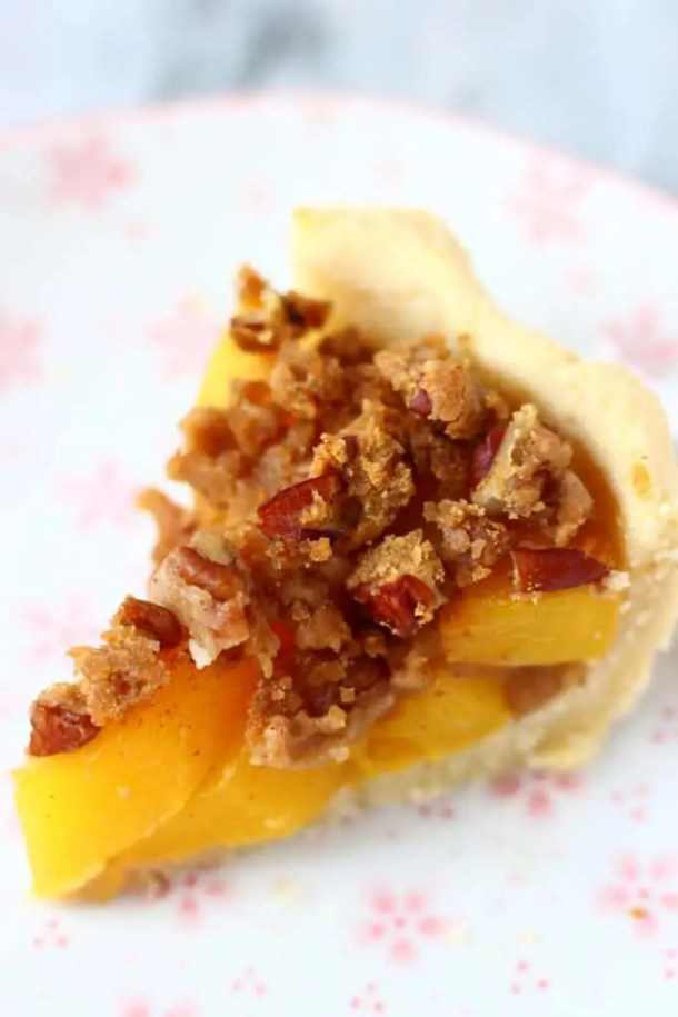 Photo of a slice of peach pie with streusel topping on a white plate