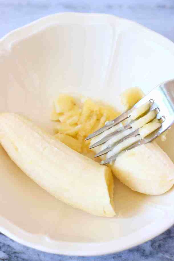 Photo of a small white bowl with a silver fork mashing a banana