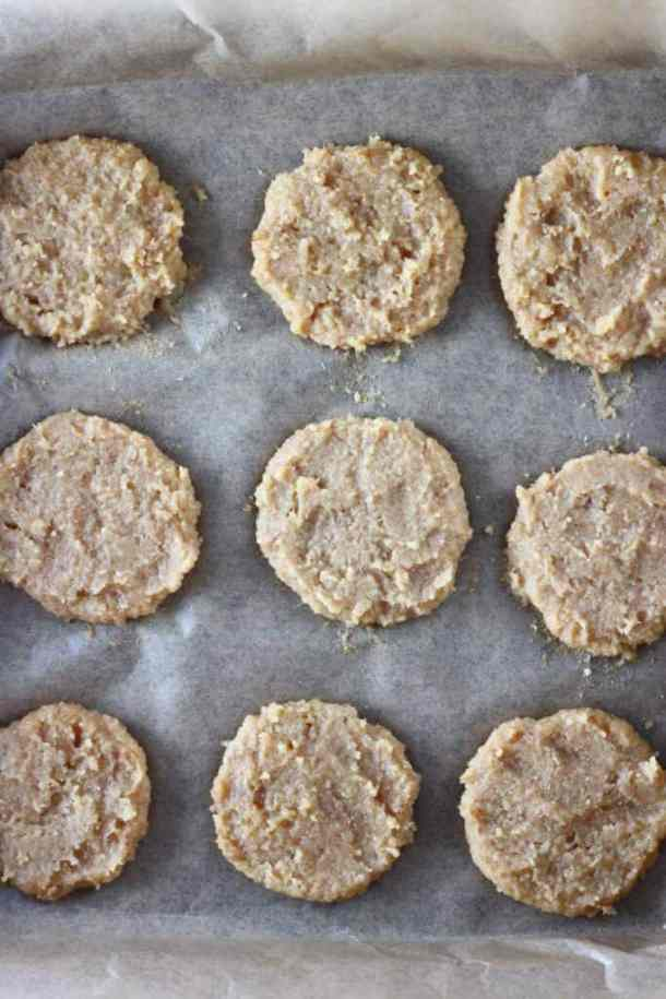Nine raw almond butter cookies on a baking tray lined with brown baking paper