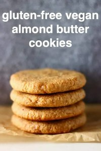 Four golden brown cookies stacked on top of each other on a sheet of brown baking paper against a grey background