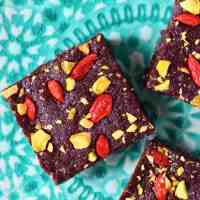 Three square brownies topped with goji berries and chopped pistachios on a green plate