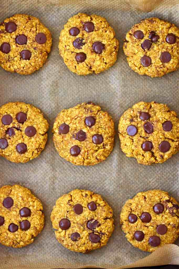 Nine pumpkin cookies studded with chocolate chips on a sheet of brown baking paper in a black baking tray