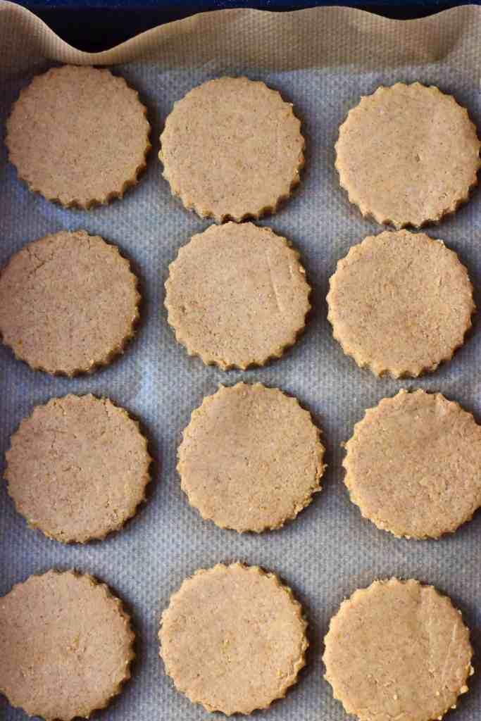 Twelve raw pumpkin cookies on a baking tray